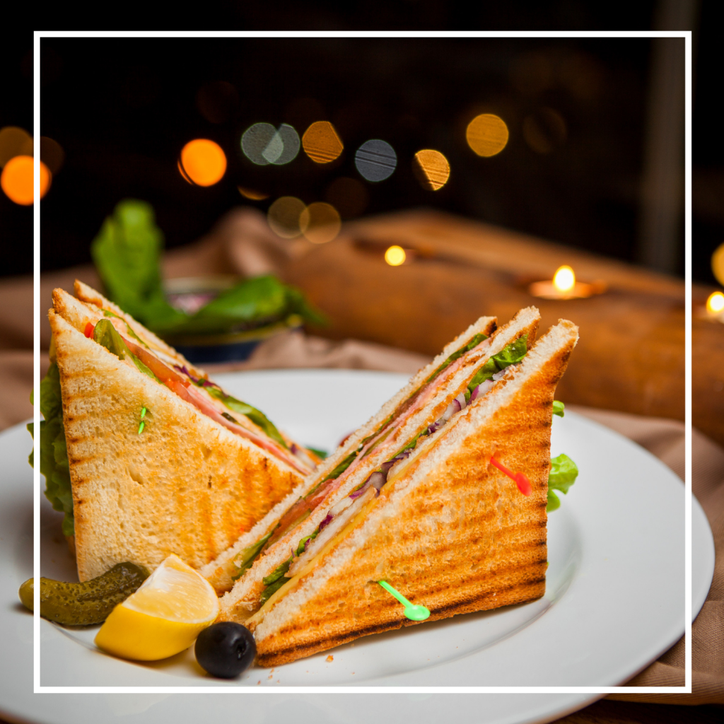 side-view-club-sandwich-with-salted-cucumbers-lemon-olives-round-white-plate-best-sandwich-press-australia